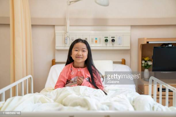 portrait of a young girl in a hospital bed - jgalione stock pictures, royalty-free photos & images