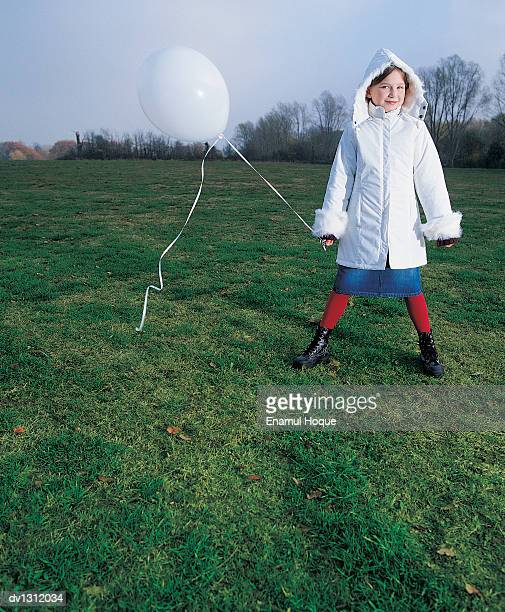 Portrait of a Young Girl in An Anorak Holding a Balloon in the Park