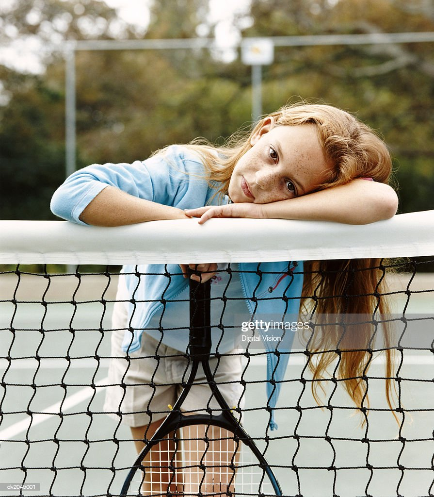 Portrait of a Young Girl Leaning on a Net in a Tennis Court : Stock Photo