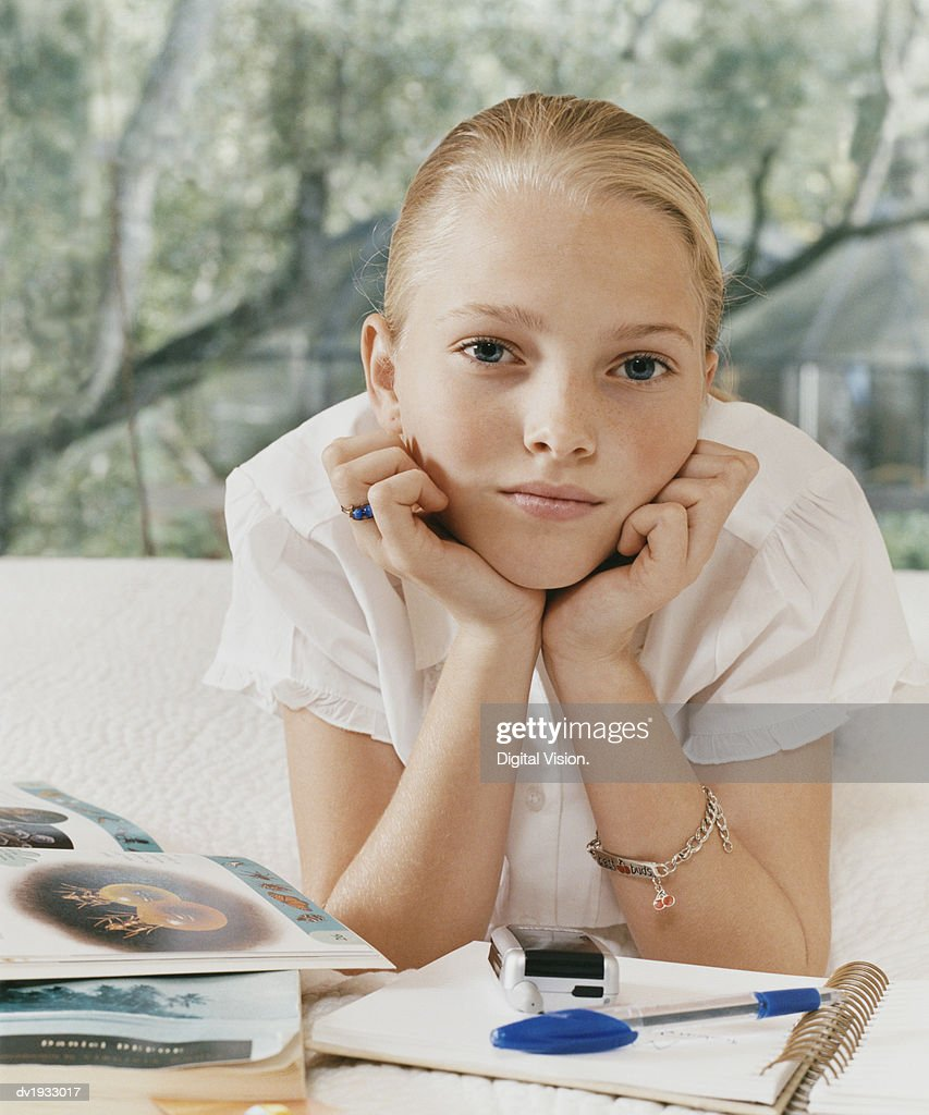 Portrait of a Young Girl Lying on Her Bed With Textbooks and a Notepad : Stock Photo