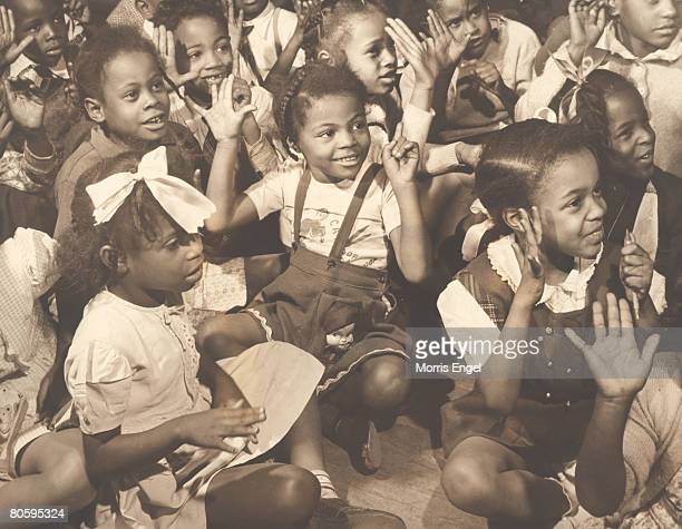 Portrait of a young girl named 'Rebecca' and her classmates sit crossed legged on the floor of the classroom and hold up six fingers in answer to an...