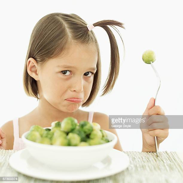 Portrait of a young girl (8-9) pouting holding a fork with a Brussels sprout