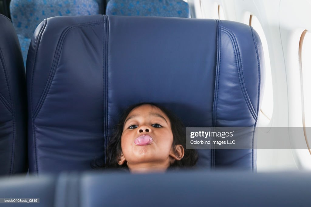 Portrait of a young girl sitting in a seat showing her tongue in an airplane : Stock Photo