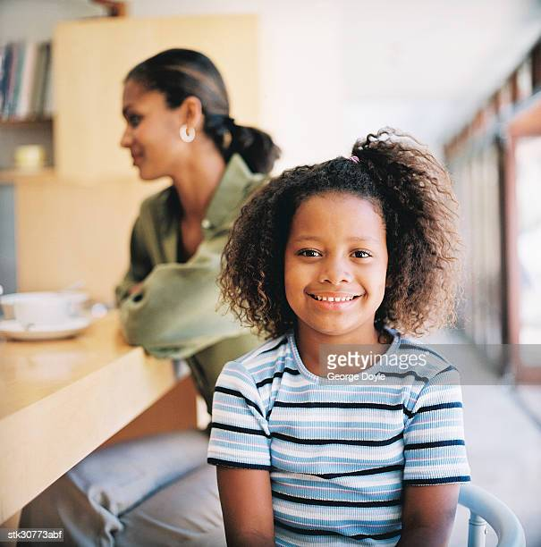 portrait of a young girl (8-10) sitting in front of her mother