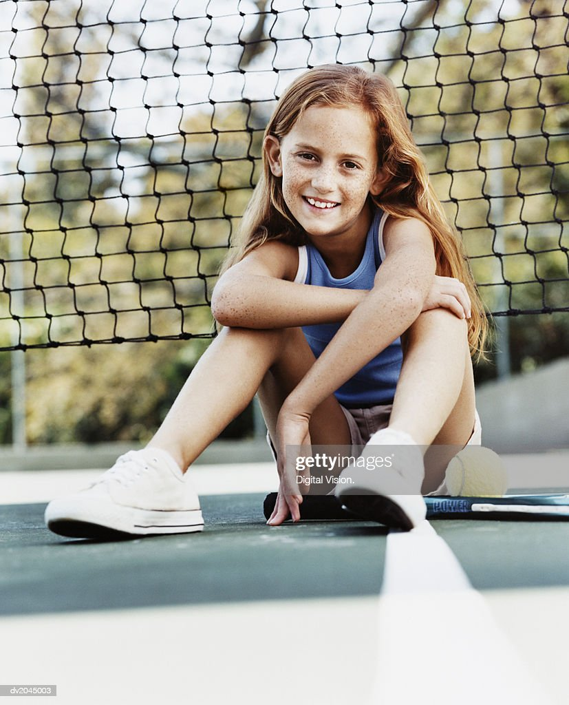 Portrait of a Young Girl Sitting on a Tennis Court by the Net : Stock Photo