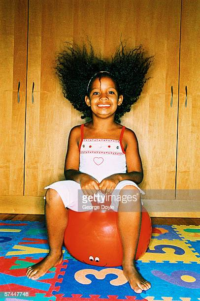 portrait of a young girl (8-10) sitting on an inflatable bouncing ball