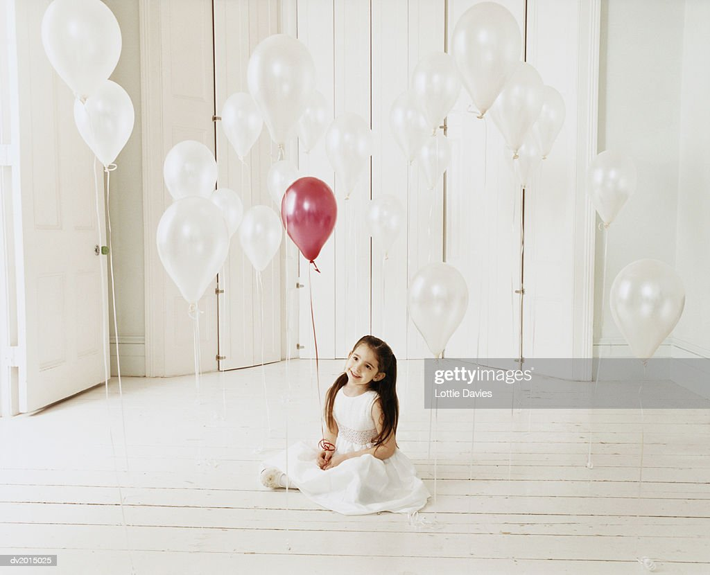 Portrait of a Young Girl Sitting on Wooden Floor Holding a Red Balloon and Looking up at White Balloons : Stock Photo