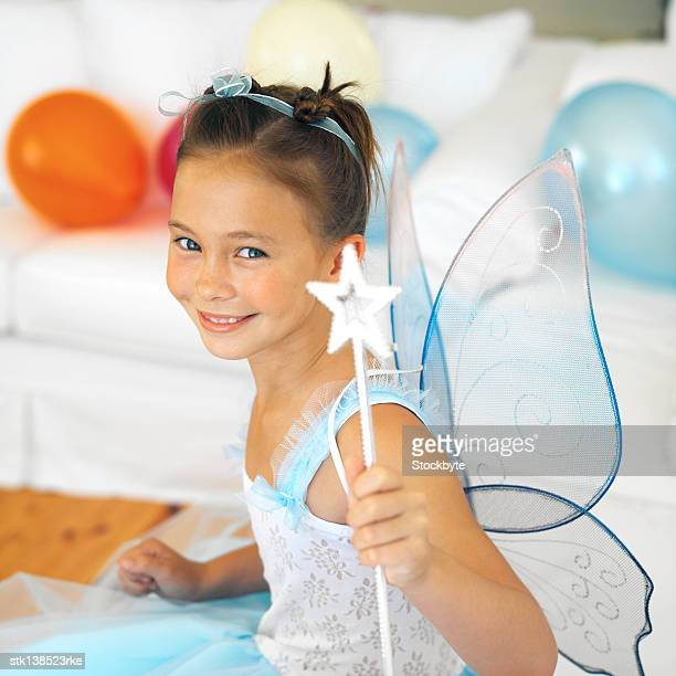 portrait of a young girl (4-6) smiling dressed up in a fairy costume