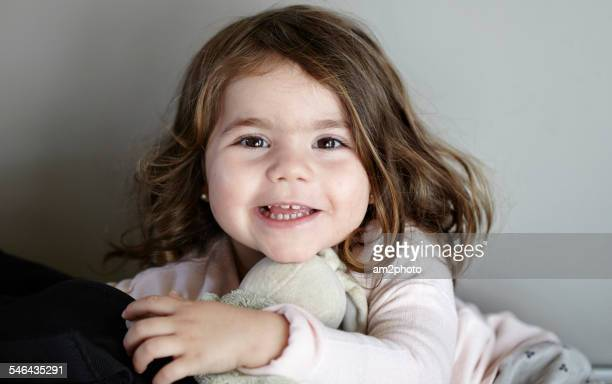Portrait of a young girl smiling with soft toy
