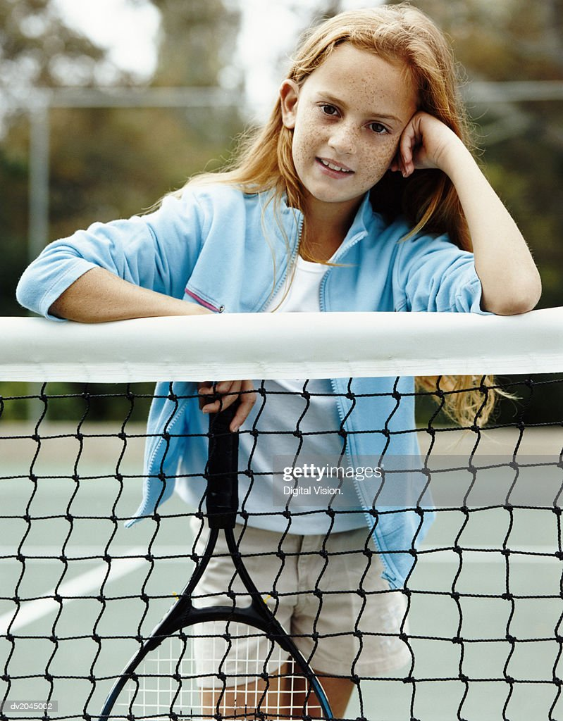 Portrait of a Young Girl Standing by the Net in a Tennis Court : Stock Photo