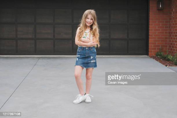 portrait of a young girl standing in front of garage door - girls with short skirts - fotografias e filmes do acervo