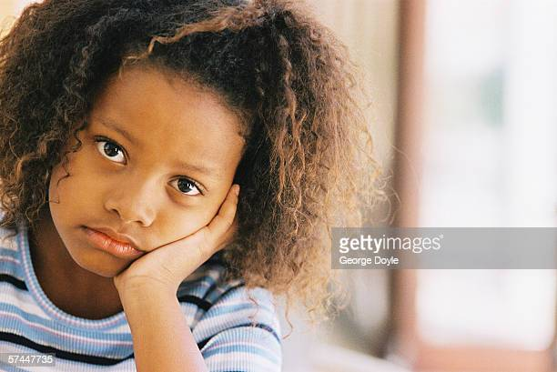 portrait of a young girl (8-10) supporting her face with her hand