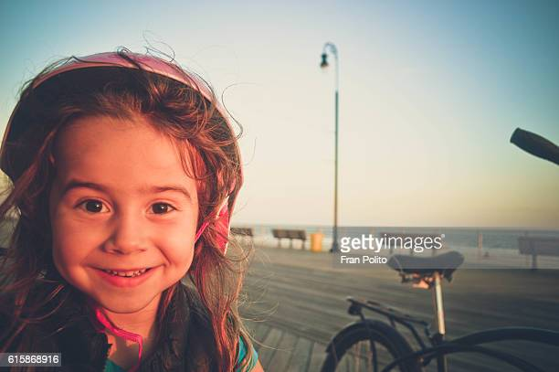 Portrait of a young girl wearing her bicycle helmet and riding her bike on the boardwalk at the beach.