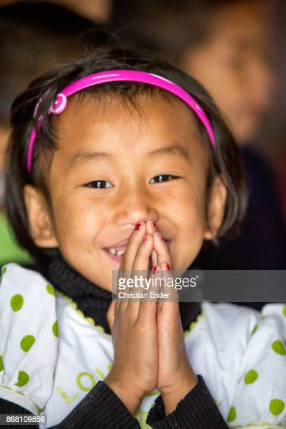 portrait of a young girl who is smiling towards the camera while she hold up her hands to pray