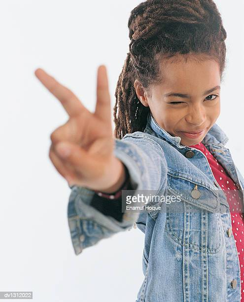 Portrait of a Young Girl Winking and Making the Peace Sign