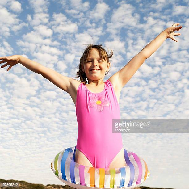 portrait of a young girl (7-8) with a rubber ring around her waist and arms stretched out - one piece swimsuit stock pictures, royalty-free photos & images