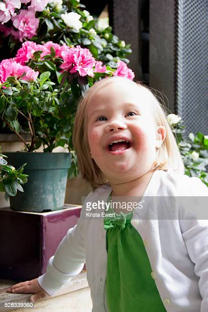 Portrait Of A Young Girl With Down Syndrome Beside Flower Pots; Vancouver British Columbia Canada