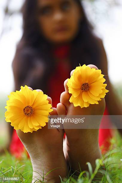 Portrait of a young girl with flowers placed between her toes