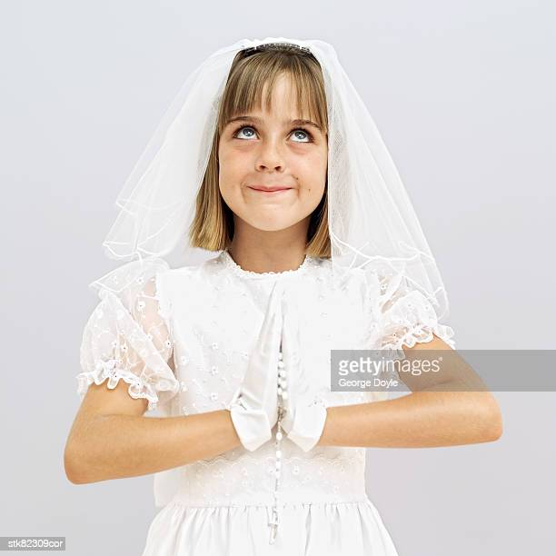 portrait of a young girl with folded hands dressed for her first holy communion