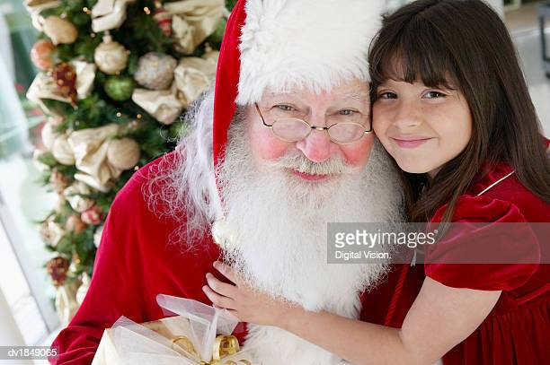 portrait of a young girl with her arm around father christmas - santa close up stock pictures, royalty-free photos & images