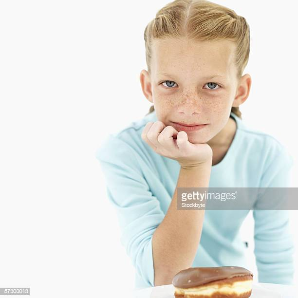 Portrait of a young girl (10-11) with her hand on her chin and a chocolate doughnut on plate