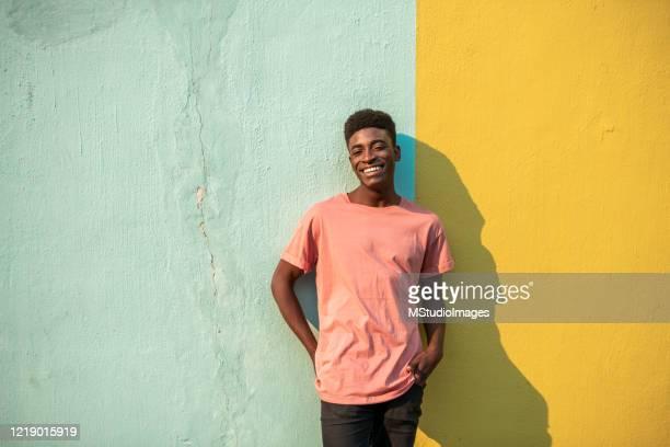 porträt eines jungen, hübschen afrikanischen mannes. - bunter hintergrund stock-fotos und bilder