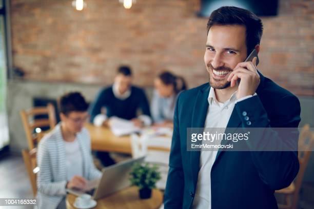Portrait d'un beau jeune homme d'affaires sur le téléphone