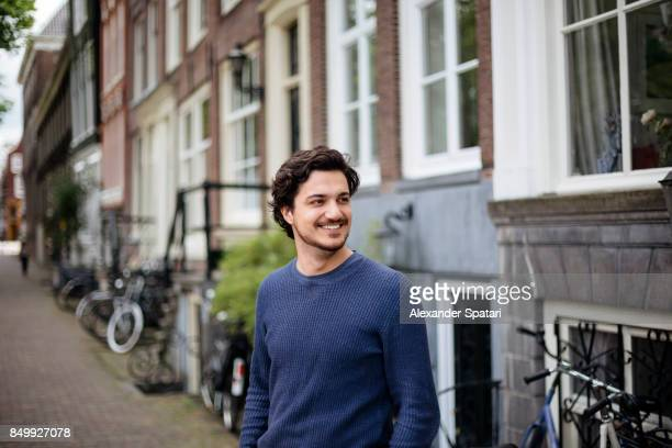 portrait of a young handsome man on the streets of amsterdam - セーター ストックフォトと画像