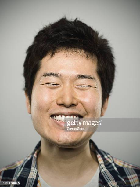Portrait of a young happy japanese man looking at camera