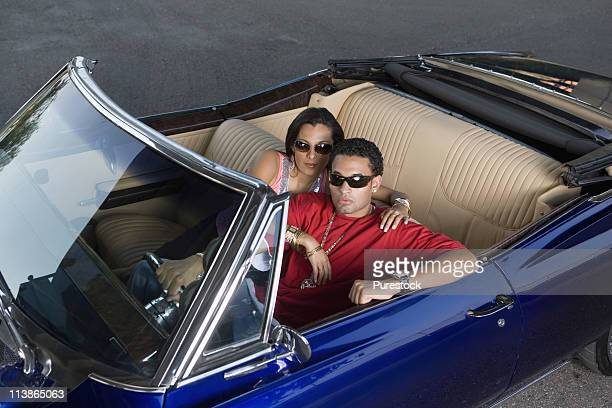 portrait of a young hip-hop couple sitting in a pimped-up vintage car - pimped car stock photos and pictures