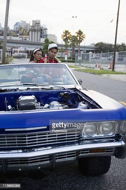 portrait of a young hip-hop couple sitting in a pimped-up vintage car in urban neighborhood - pimped car - fotografias e filmes do acervo