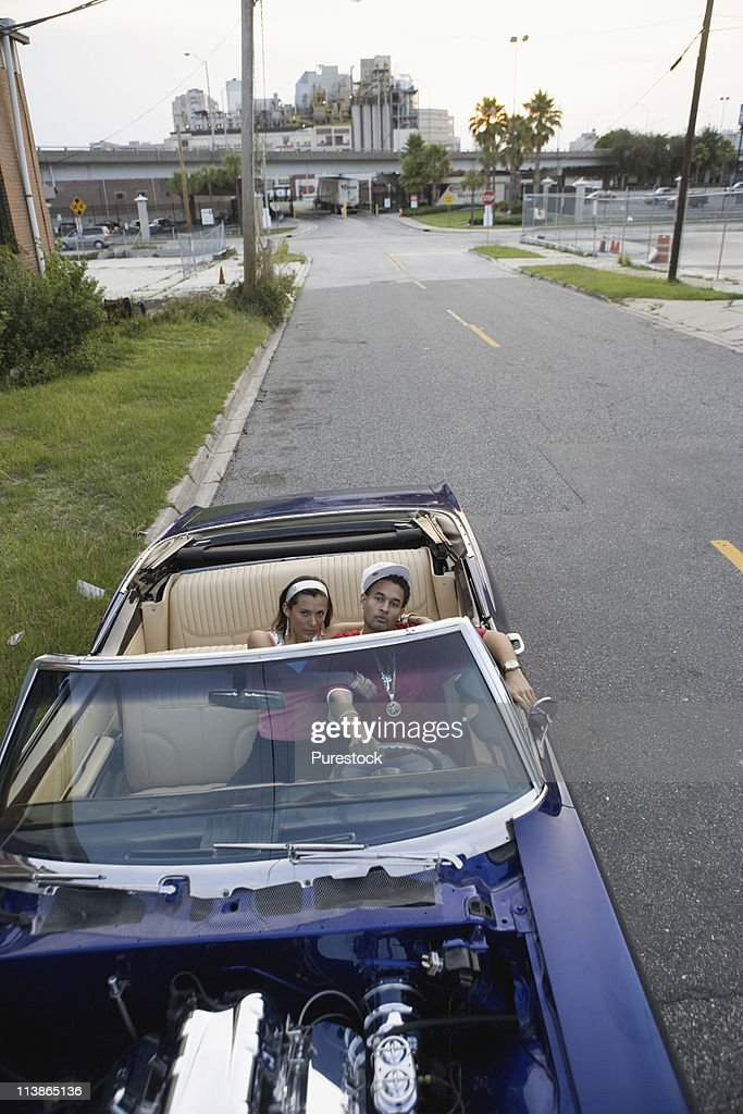 Portrait of a young hip-hop couple sitting in a pimped-up vintage car in depressed urban neighborhood : Foto de stock