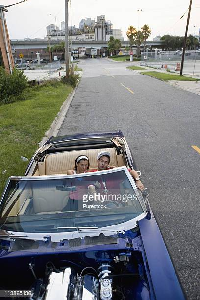 portrait of a young hip-hop couple sitting in a pimped-up vintage car in depressed urban neighborhood - pimped car stock photos and pictures