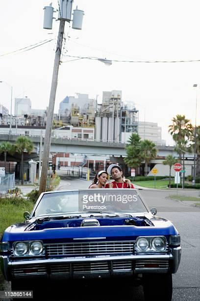 portrait of a young hip-hop couple sitting in a pimped-up vintage car in depressed urban neighborhood - pimped car - fotografias e filmes do acervo