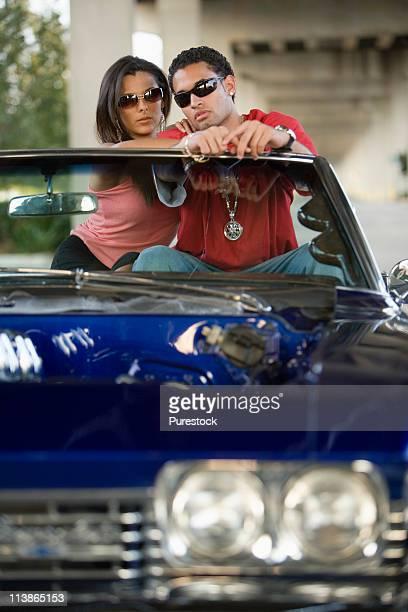 portrait of a young hip-hop couple sitting in a pimped-up vintage car - pimped car - fotografias e filmes do acervo