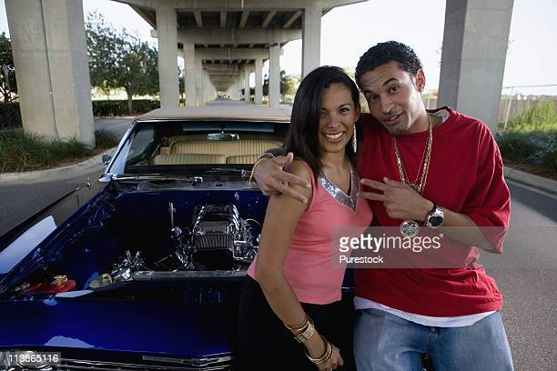 portrait of a young hip-hop couple standing beside a pimped-up vintage car - pimped car - fotografias e filmes do acervo