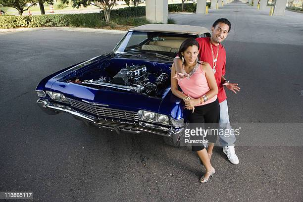 portrait of a young hip-hop couple standing beside a pimped-up vintage car - pimped car stock photos and pictures