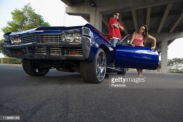 portrait of a young hip-hop couple standing beside a pimped-up vintage car under a highway overpass - pimped car stock photos and pictures