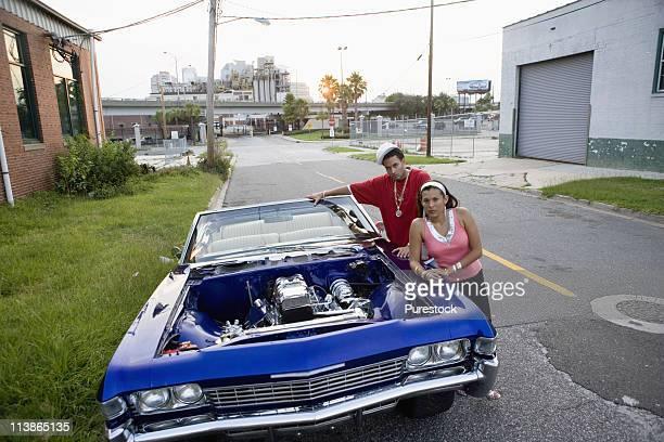 portrait of a young hip-hop couple standing beside a pimped-up vintage car in depressed urban neighborhood - pimped car - fotografias e filmes do acervo