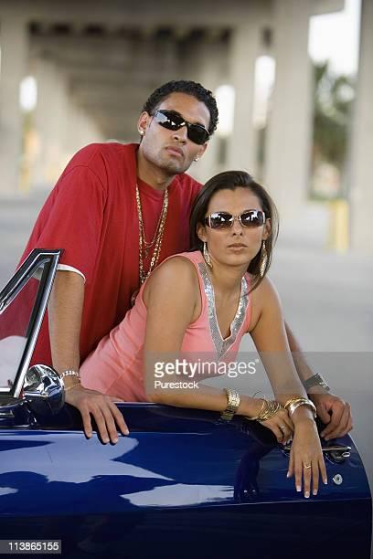 portrait of a young hip-hop couple standing beside a pimped-up vintage car under a highway overpass - pimped car - fotografias e filmes do acervo