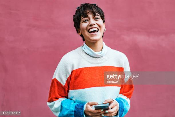portrait of a young hipster girl holding phone - short hair stock pictures, royalty-free photos & images