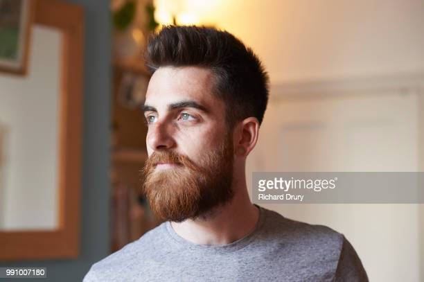 portrait of a young hipster man in his living room - beard stock pictures, royalty-free photos & images