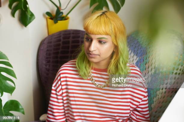 Portrait of a young hipster woman sitting in an armchair