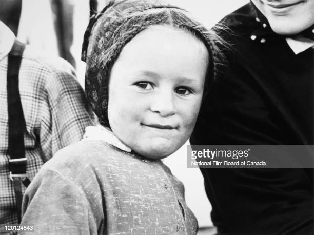 Portrait of a young Hutterite girl with her smiling mother standing by her side Northeast Alberta Canada 1963 Photo taken during the National Film...