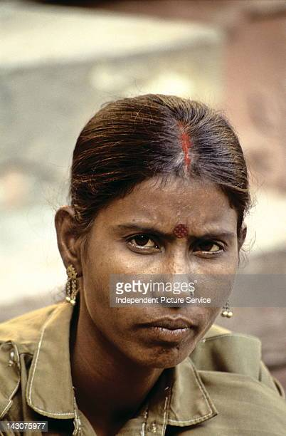 Portrait of a young Indian woman with the traditional ornamental marks of a bindi and sindoor India