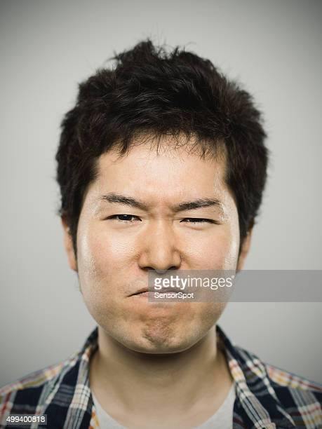 Portrait of a young japanese angry man looking at camera