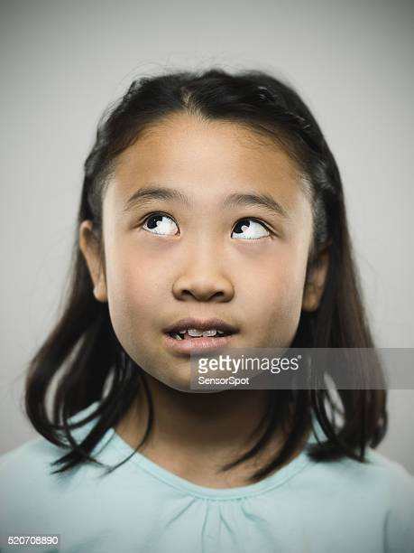 Portrait of a young japanese girl looking up.