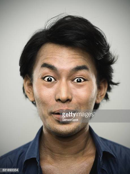 Portrait of a young japanese man looking at camera.