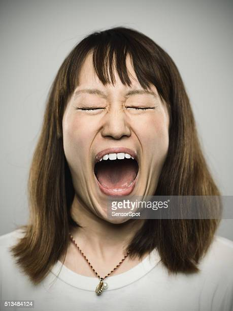 Portrait of a young japanese woman screaming.
