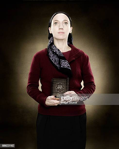 portrait of a young jewish woman holding a prayer book - prayer book stock pictures, royalty-free photos & images